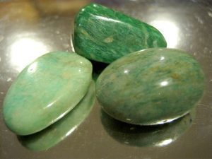 3 color green shiny stones on the table