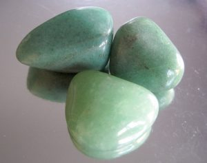 3 green aventurine stone on a glass table