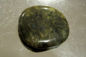 a flat garnet green stone on the stainless table