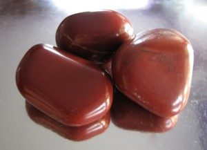 3 color red jasper smoth stone on a shiny table