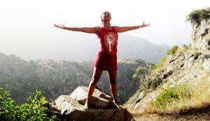 an image of a women wearing a pink t-shirt and a short red lower standing on a rock while rasing both her hands in the mountain