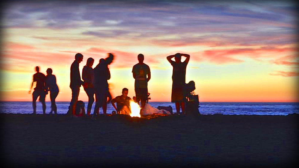 8 people in the beach camping smiling in front of the fire